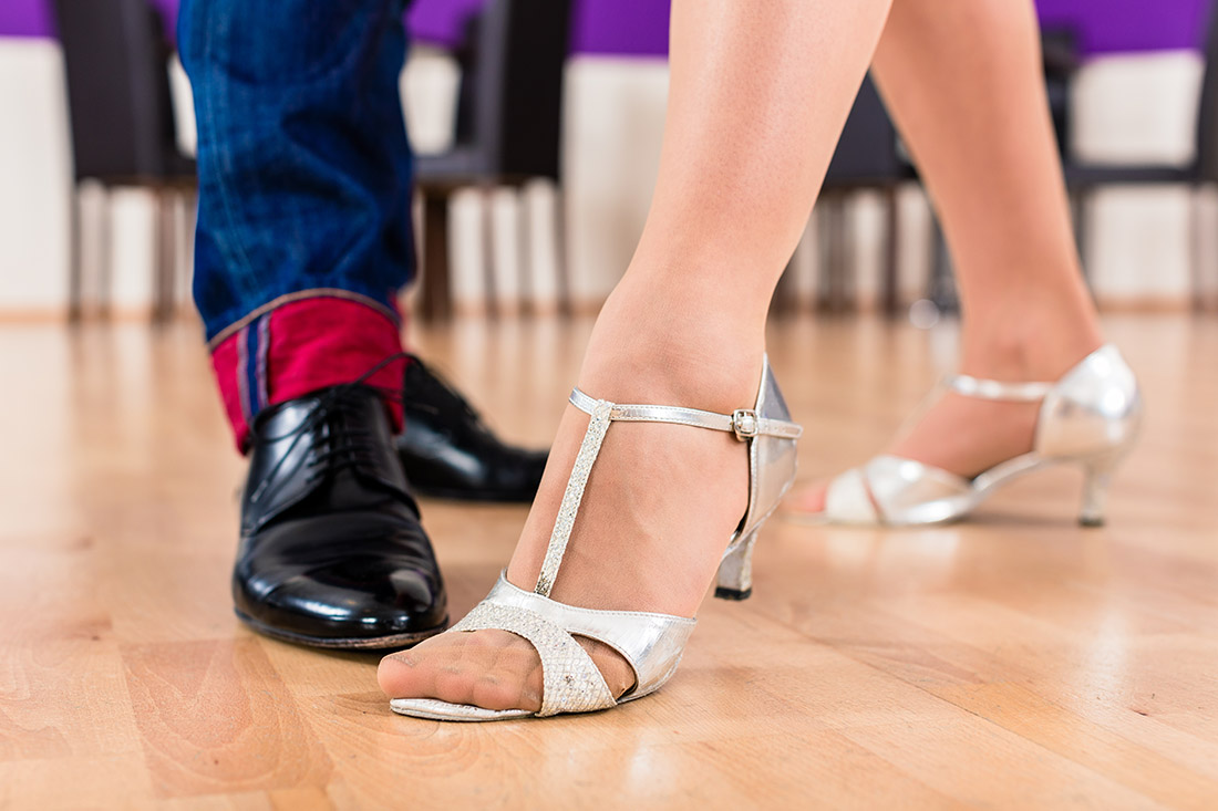 Woman and man with her dancing shoes in dance school
