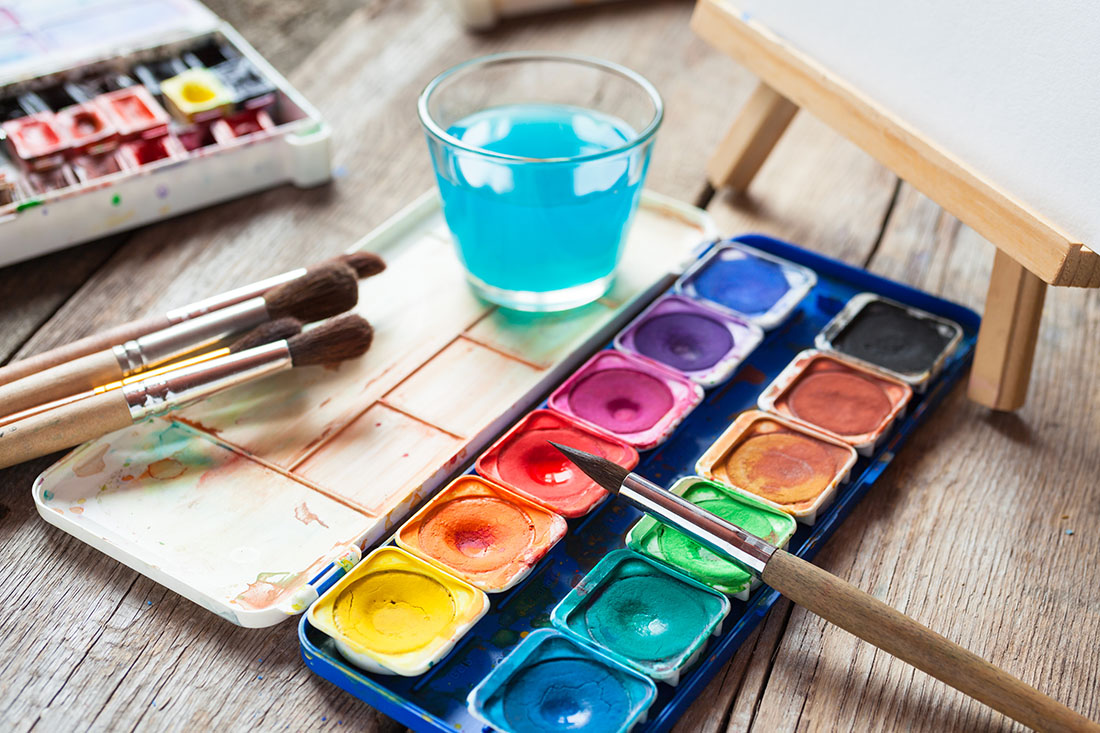 Set of watercolor paints art brushes glass of water and easel with painting on old wooden table.